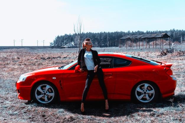 サングラスをかけたゴージャスな若いスリムな女性は、フィールドで赤いスポーツカーと一緒に立っています