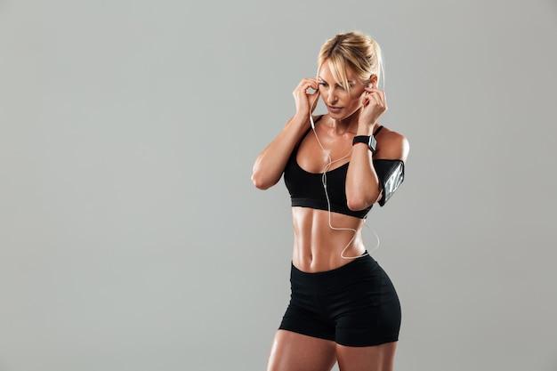音楽を聴いて立っている豪華な若いスポーツ女性