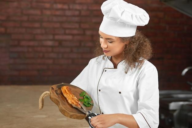 Великолепный шеф-повар молодой женщины, работающий в своем ресторане, готовит куриный стейк, режущий мясо ножницами.