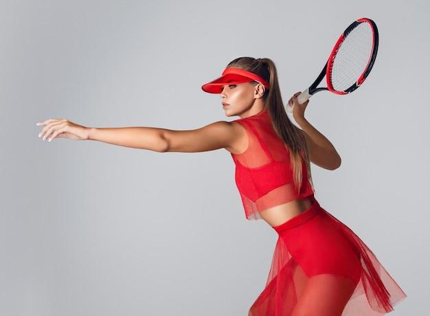真っ赤なスポーツ服を着たゴージャスな若い女性が、打ち負かす準備ができているテニスラケットを持っています。スポーツ、テニス、体の彫刻、スポーツゲーム、美容、ファッション。