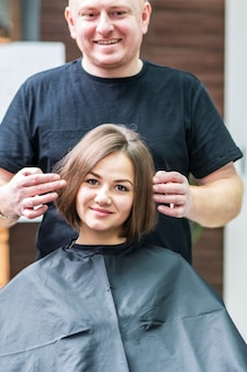 Gorgeous young woman and her hairdresser smiling looking in the mirror in hair salon.