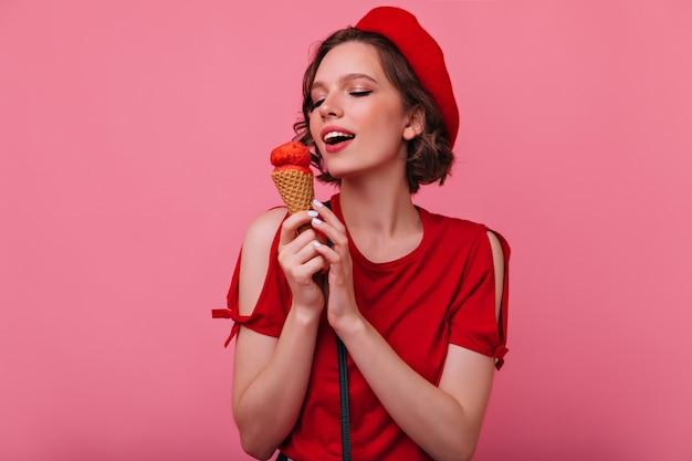 アイスクリームを食べる赤い服のゴージャスな若い女性。デザートでポーズをとる洗練されたフランスの女性モデル。