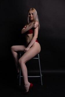 Великолепная молодая женщина в красном кружевном нижнем белье сидит на стуле