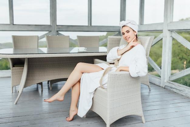 흰색 가운을 입은 멋진 젊은 여성이 집의 여름 테라스에 앉아 있습니다. 아침 개념입니다.
