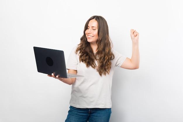 ゴージャスな若い女性がノートパソコンを持って勝者のジェスチャーをしています。