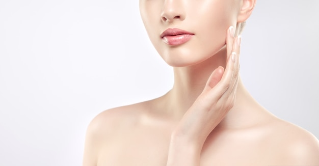 Gorgeous, young woman is touching soft skin of the face by graceful fingers of hand