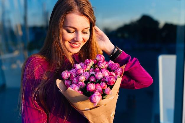 ゴージャスな若い女性が幸せそうに笑って花の花束を見て