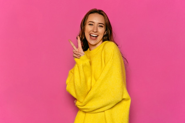 Gorgeous young woman showing peace gesture, dressed in yellow sweater.