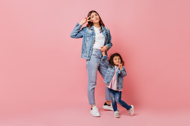 Gorgeous young woman spending time with little daughter. attractive mother in jeans holding hands with child.