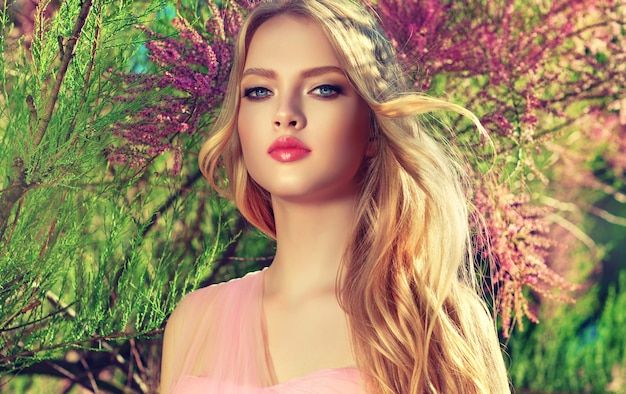 Gorgeous young woman surrounded by blossoming garden trees, light wind in her long curly blonde hair. gentle makeup with rose lipstick and hairstyling. blossom of youth. spring style.