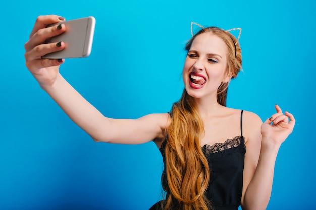 Bellissima giovane donna prendendo selfie, rendendo divertente l'espressione del viso, mostrando la lingua, alla festa. ha lunghi capelli biondi, un bel trucco. indossa un abito nero, diadema con orecchie di gatto.