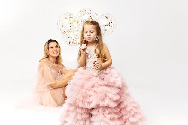 그녀의 딸과 함께 생일을 축하하는 낮은 목 끈이없는 드레스를 입고 화려한 젊은 여자