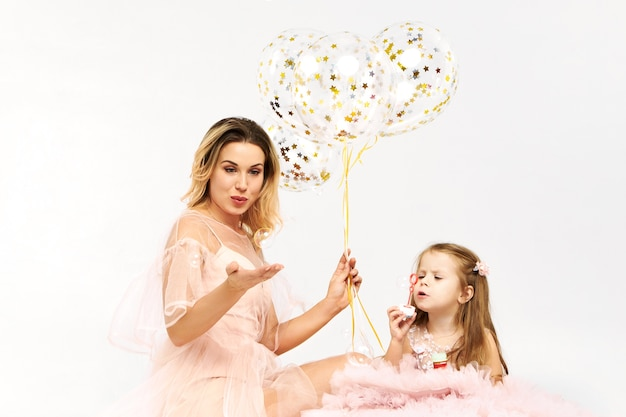 Gorgeous young woman wearing low neck strapless dress celebrating birthday with her daughter