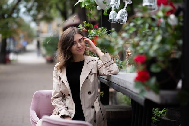 멋진 젊은 여성은 아침에 거리 카페에 앉아 베이지색 코트를 입고 있습니다. 녹색과 꽃으로 된 외부 장식. 빈 공간