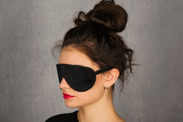 Великолепная молодая женщина с черной маской сна e