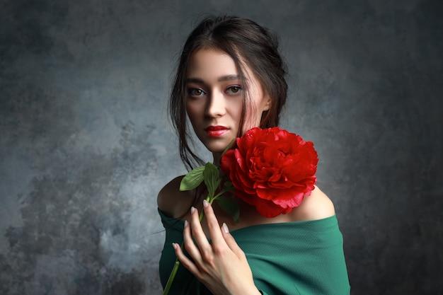 牡丹の花でポーズ明るいメイクでゴージャスな若い女性。香水と化粧品。ファッションコンセプト