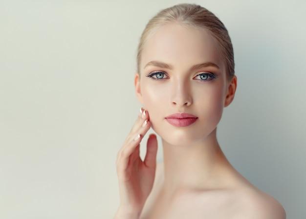 깨끗하고 상큼한 피부, 부드러운 메이크업, 입술에 장미 립스틱을 가진 화려하고 젊은 여성이 얼굴을 만지고 있습니다.