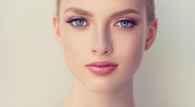 깨끗하고 신선한 피부를 가진 화려하고 젊고 여성, 길고 완벽한 속눈썹과 장미 립스틱으로 부드러운 메이크업