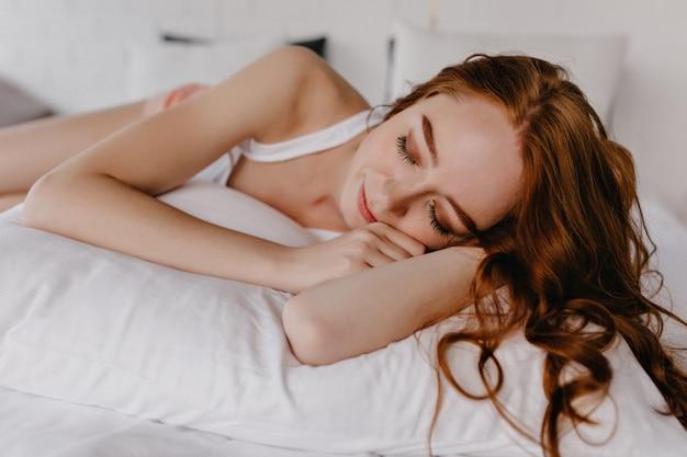 그녀의 방에서 자고 곱슬 헤어 스타일으로 화려한 젊은 여자. 눈을 감고 베개에 누워 매혹적인 백인 여자.