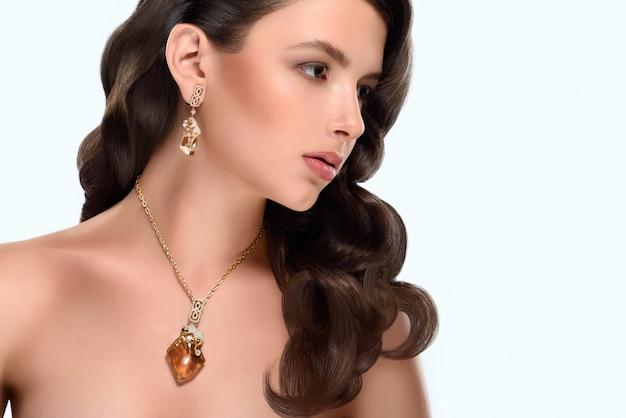 Copyspaceと金色の宝石を身に着けているよそ見健康的な光沢のあるウェーブのかかった長い髪を持つ豪華な若い女性