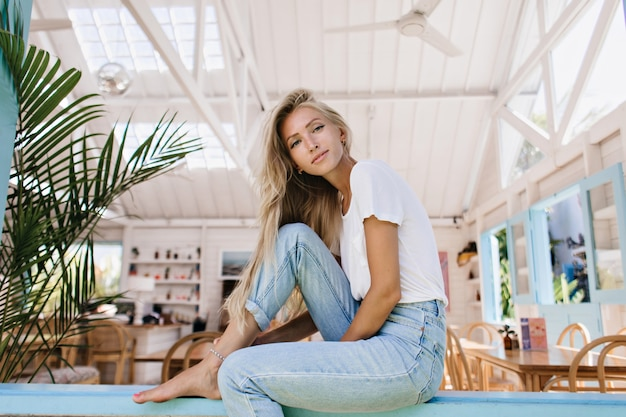 カフェテリアでポーズをとる明るい髪のゴージャスな若い女性。窓枠に座っている青いデニムパンツの洗練された女性モデルの肖像画。
