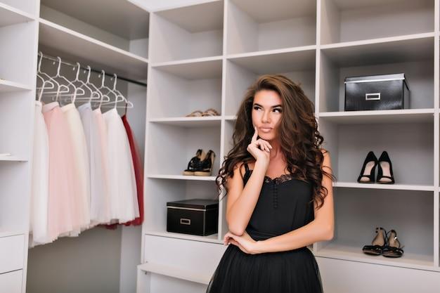 Bellissima giovane donna con lunghi capelli ricci castani pensando a cosa indossare nel grande guardaroba, modello alla moda in cerca di vestiti, sguardo premuroso. indossare un abito nero elegante.