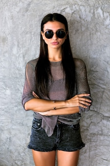 Gorgeous young woman with long brunette hair in black stylish sunglasses, shorts and transparent t-shirt on gray wall