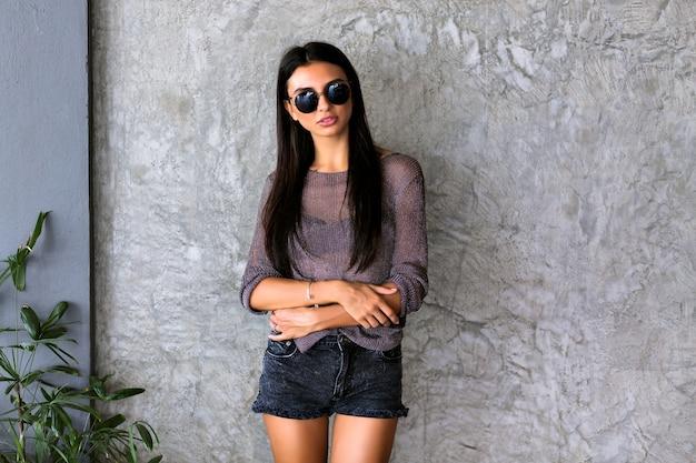 黒のスタイリッシュなサングラス、ショートパンツ、灰色の壁に透明なtシャツの長いブルネットの髪を持つゴージャスな若い女性