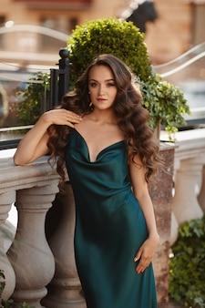 夏の晴れた日に屋外でポーズをとる流行のサマードレスを着て完璧なメイクでゴージャスな若い女性