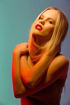 赤い唇立って自分を抱いてゴージャスな若い女性