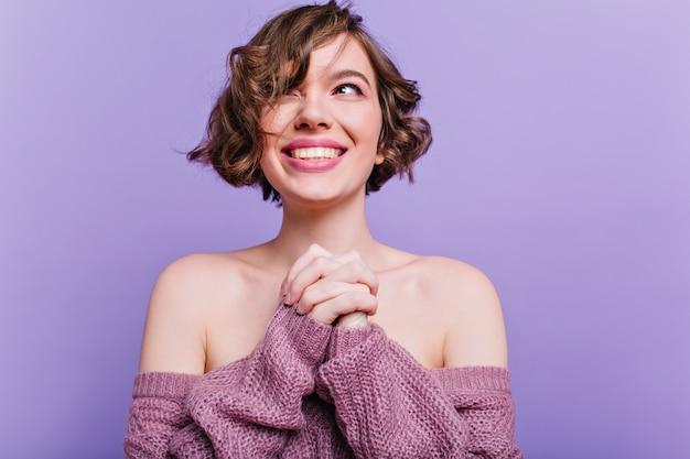 喜んで笑顔でポーズをとる短い散髪のゴージャスな若い女性。紫色の壁に立っているウールのセーターを着たエレガントな黒髪の少女の屋内写真。
