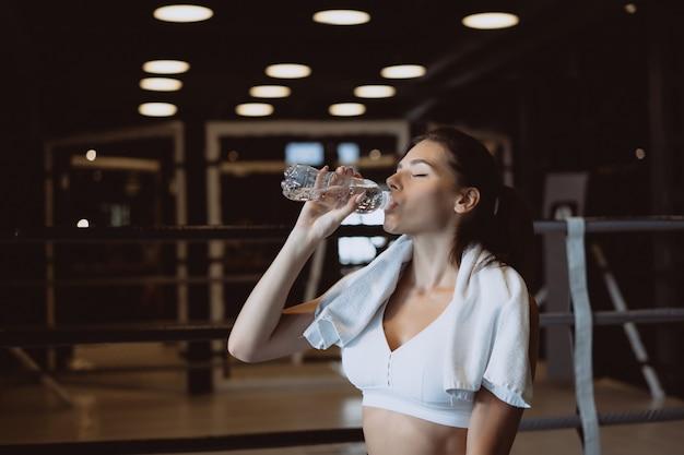 Giovane donna splendida con un asciugamano sulle sue spalle acqua potabile da una bottiglia alla palestra