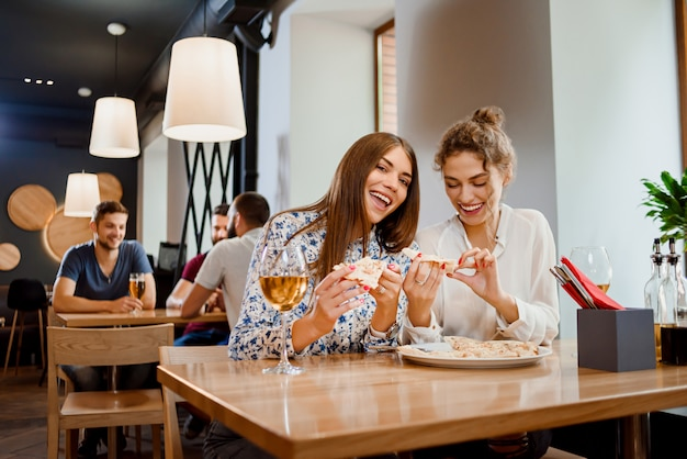 Gorgeous young women eating pizza in restaurant.