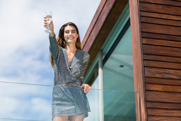 Gorgeuos woman showing champagne flute at balcony