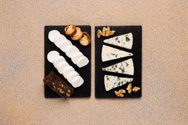 Gorgonzola cheese slices and walnut with goat cheese; brown cheese and bread on black slate stone over textured wallpaper