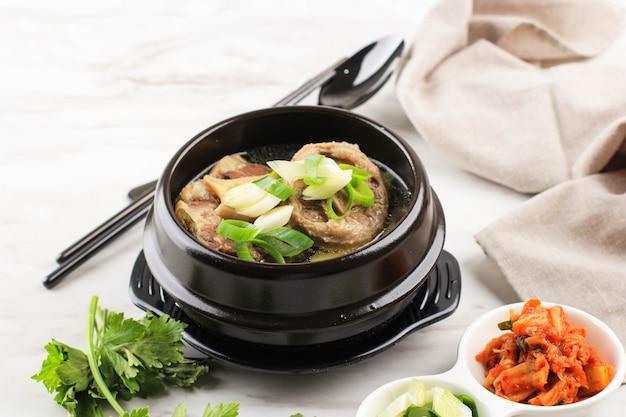 Гори гомтанг (соккори гомтанг) или суп с тушеным мясом из говядины по-корейски, подается в черной корейской миске с кимчи и нарезанным зеленым луком