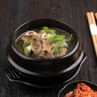 고리 곰탕(속꼬리 곰탕) 또는 한우 소꼬리 스튜, 김치와 파를 곁들인 검은 한국 그릇에 제공