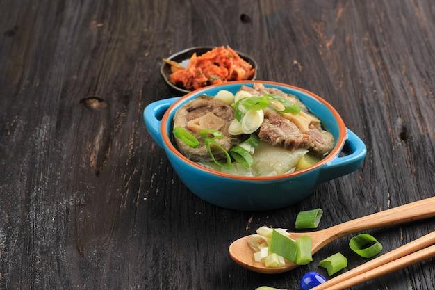 Гори гомтанг (соккори гомтанг) или суп с тушеным мясом из говядины по-корейски, подается в синей миске с кимчи и нарезанным зеленым луком, место для текста на черном деревянном столе. закройте вверх.