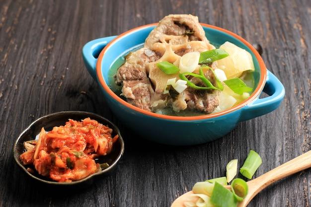고리 곰탕(속꼬리 곰탕) 또는 한국 쇠고기 소꼬리 스튜 수프는 파란색 그릇에 김치와 얇게 썬 파와 함께 제공되며 검은 나무 테이블에 텍스트를 위한 공간을 복사합니다. 확대.
