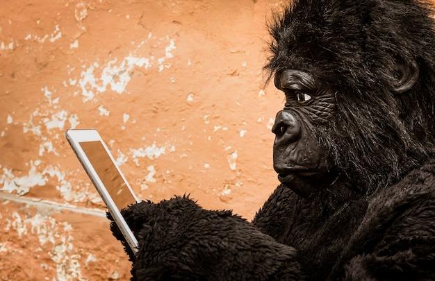 새로운 현대 생활 기술에 대한 동물 적응의 개념을 나타내는 태블릿이 있는 고릴라