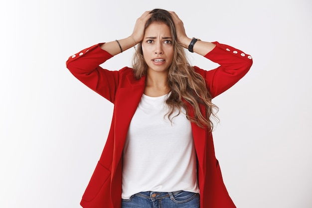 Gosh have trouble. portrait of panicking worried young cute silly female trainee wearning red jacket holding hands head distressed nervous widen eyes perplexed, having problem white wall