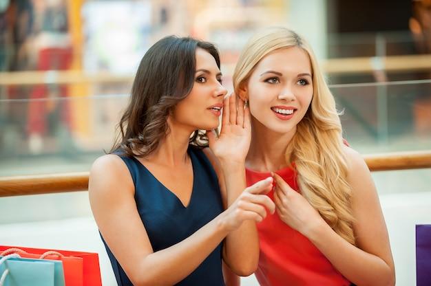Сплетничать. две красивые молодые женщины сплетничают во время покупок в торговом центре