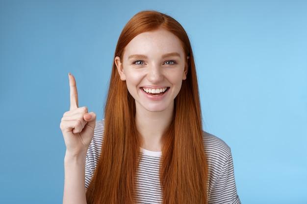 Есть отличная идея для вас. привлекательная, счастливая, дружелюбная, полезная рыжая женщина-продавец, показывающая покупателя в великолепном платье, указывая вверх указательным пальцем, улыбаясь, рада помощи, синий фон