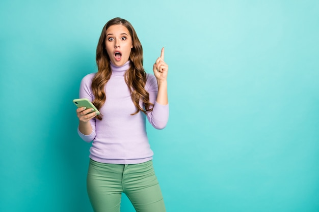 Got it! photo of beautiful shocked lady hold telephone hands have creative post idea raise finger intelligent person wear purple pullover green pastel pants isolated teal color