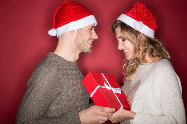 Got something for you. horizontal portrait of a young handsome man in a christmas hat giving present to his beautiful happy girlfriend