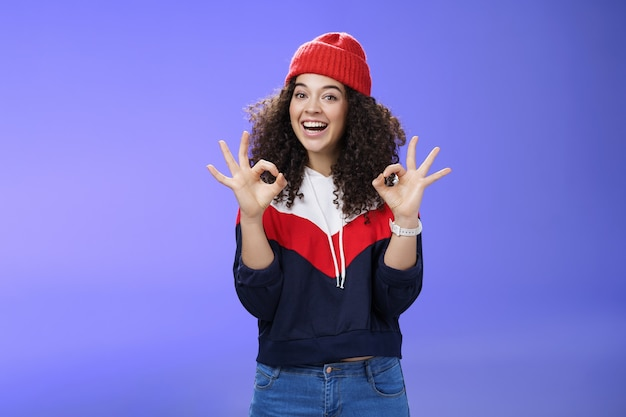 制御下に置かれました。暖かい冬の帽子とスウェットシャツを着た幸せで魅力的な笑顔の縮れ毛の女性の肖像画は、広く笑顔で、クールな動きが好きで、承認として大丈夫または優れたジェスチャーを示しています。