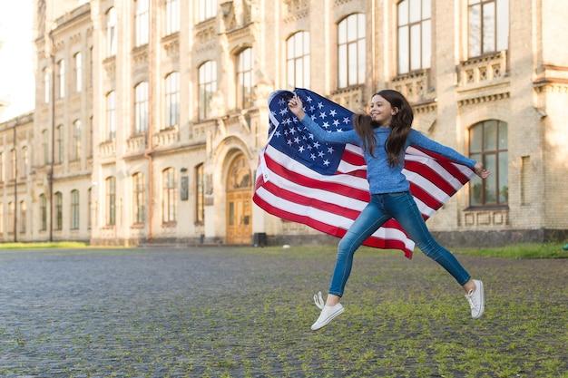 アメリカビザを取得しました。幸せな女の子はアメリカの国旗でジャンプします。ビザ申請者。ビザ申請。移民と市民権。駐在と移住の自由。 7月4日。独立記念日。ビザ免除旅行。