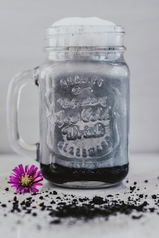 Goth latte with charcoal and milk in a jar. selective focus