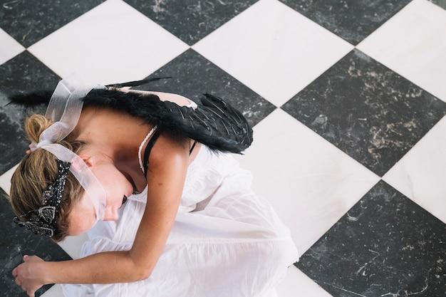 Gothic angel lying on floor Free Photo