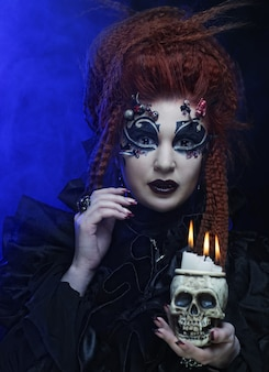 Gothic vampire redhair  woman with skull.